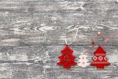 Hintergrund mit roten Weihnachtsdekorationsbäumen auf grauem hölzernem b Stockfotos