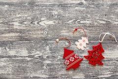 Hintergrund mit roten Weihnachtsdekorationsbäumen auf grauem hölzernem b Lizenzfreie Stockbilder