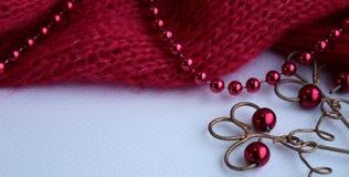 Hintergrund mit schöner Metallschneeflocke und gestricktem rotem Bahnstoff auf einem hellen Hintergrund stockbild