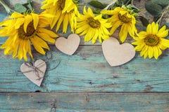 Hintergrund mit Sonnenblumen und Herzen auf alten hölzernen Brettern mit PET Stockfotografie