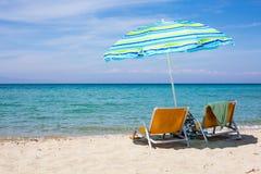 Hintergrund mit Strandstühlen und bunter Regenschirm auf sandigem Strand Stockfoto