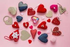 Hintergrund mit unterschiedlichem Gewebe und hölzerne Herzen auf einem rosa BAC Stockfoto