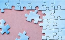 Hintergrund mit verbundenen Stücken des blauen Puzzlespiels Stockfotos