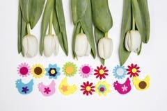 Hintergrund mit weißen Tulpen und lustigen Zahlen von Hühnern und von Blumen vom Filz Seemöwe, die auf einem Flussrand steht Lizenzfreies Stockbild