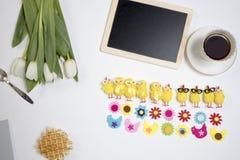 Hintergrund mit weißen Tulpen und lustigen Zahlen von Hühnern und von Blumen vom Filz Seemöwe, die auf einem Flussrand steht Lizenzfreies Stockfoto