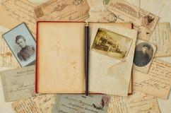 Hintergrund mit Weinlesefoto, Postkarte und leerem offenem Buch lizenzfreie stockfotografie