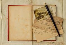 Hintergrund mit Weinlesefoto, Postkarten und leerem offenem Buch Stockfoto