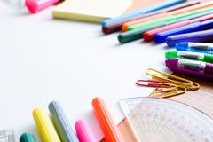Hintergrund-Papier, farbige Bleistifte, Stifte, Markierungen und etwas Kunstmaterial auf gemalter Holzoberfläche Stockfotos