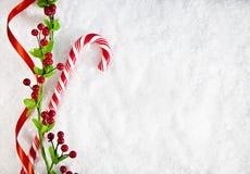 Hintergrund Süßigkeits-Cane With Christmas Decoration Ons Snowy Lizenzfreies Stockfoto