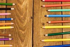 Hintergrund von bunten Bleistiften auf altem Holztisch Lizenzfreies Stockfoto