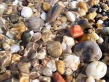 Hintergrund von den bunten Seekieseln, -wasser und -schaum Lizenzfreie Stockfotografie
