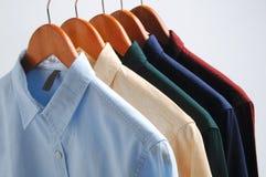 Hintergrund von den Hemden, die an einem Aufhänger hängen stockbilder