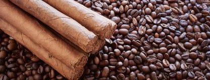 Hintergrund von den Kaffeebohnen mit den kubanischen Zigarren lizenzfreie stockfotografie