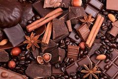 Hintergrund von den Scheiben der Schokolade, der Nüsse und der Gewürze Stockfotografie
