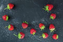 Hintergrund von Erdbeeren auf schwarzem Stein mit Zucker Lizenzfreie Stockfotos