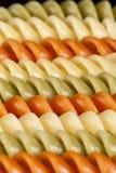 Hintergrund von farbigen gewundenen Teigwaren, Muster Lizenzfreie Stockfotografie