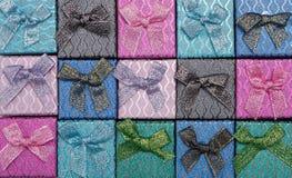 Hintergrund von farbigen quadratischen Geschenkboxen mit Bögen Stockfotografie
