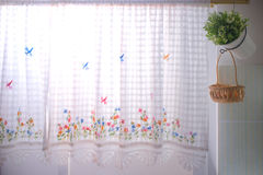 Hintergrund von Küchenfenstern kleidete mit Spitzengardine- und Blumentopf an Stockbild
