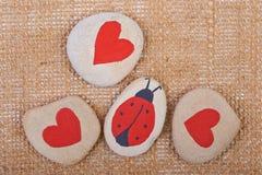 Hintergrund von Kieseln mit Herzen und von Marienkäfer gemalt Stockbilder