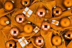 Hintergrund von orange Christbaumkugeln, von kleinen Geschenkboxen und von Golddekorationen auf orange Seidengewebe Lizenzfreie Stockfotos