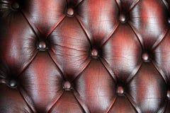 Hintergrund von reichem Burgunder färbte Leder und Knöpfe Stockbilder