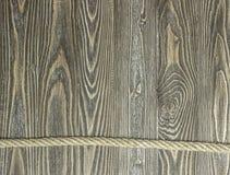 Hintergrund von strukturierten Kiefernplanken und -seil auf hölzernen Planken Stockbild