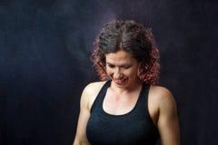 Hintergrundbeleuchtete Kreide muskulöser weiblicher Trainer-Looking Down Withs alles Arou Lizenzfreie Stockfotografie