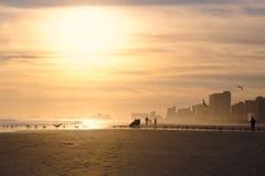 Hintergrundbeleuchtete Strand-Szene bei Sonnenuntergang Lizenzfreie Stockfotos