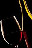 Hintergrundbeleuchtetes Detail eines Glases des Rotweins und der Weinflasche Stockbilder