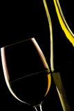 Hintergrundbeleuchtetes Detail eines Glasweins und der Weinflasche Stockfoto
