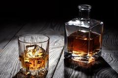 Hintergrundbeleuchtetes Glas Whisky mit Eis Stockfoto