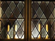 Hintergrundbeleuchtetes Kirchenfenster mit Kerzen nach innen stockfotografie