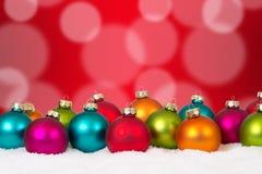 Hintergrunddekoration vieler bunte Weihnachtsbälle mit Schnee Stockfotos