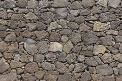 Hintergrundfassade des vulkanischen Felsens des Basalts im warmen Ton Stockbild