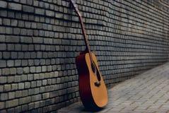 Hintergrundgitarren-Backsteinmauerkünstler Stockfoto