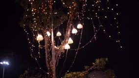 HintergrundGlühlampen im Freien auf einem Draht gegen Dämmerungswald, Feiertagskonzept stockbilder