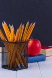 Hintergrundtafelkreide, Bücher, Bleistifte und Apfel Stockfotos