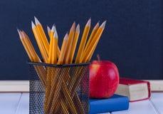 Hintergrundtafelkreide, Bücher, Bleistifte und Apfel Lizenzfreie Stockfotografie