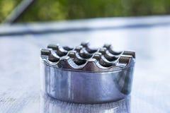 Hintergrundunschärfe-Metallaschenbecher auf der Oberfläche der Tabelle Stockbild