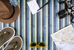 Hintergrundzusammensetzung von oben für Sommerferien mit Weinlesekamera, -Sonnenbrille, -Flipflops, -strohhut, -karte und -notizb lizenzfreie stockbilder