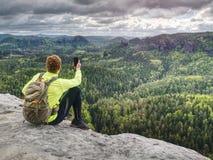 Hinterläufer macht Pause, macht Fotos durch sein intelligentes Telefon stockfotografie