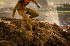 Hinterlaufende Athletenüberfahrt die schmutzige Pfütze in einem Schlammrennläufer stockbild