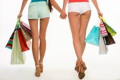 Hinterteile von den Mädchen, die Einkaufstaschen halten Lizenzfreies Stockfoto