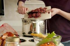 Hinzufügen des Rindfleisches mit Schneidebrett Suppentopf Stockfoto