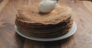 Hinzufügen des Sauerrahms auf Pfannkuchen oder Blini Stockfoto