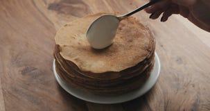 Hinzufügen des Sauerrahms auf Pfannkuchen oder Blini Stockbilder