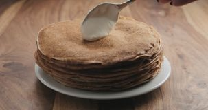Hinzufügen des Sauerrahms auf Pfannkuchen oder Blini Stockbild