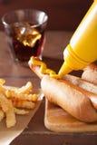 Hinzufügen des Senfes gegrilltem Hotdog Lizenzfreie Stockfotos