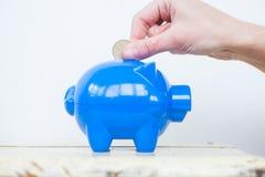 Hinzufügen von Münzen dem Sparschwein Stockfoto