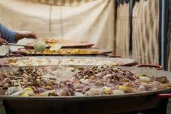 Hinzufügen von Meeresfrüchten enormen Bratpfannen Leute bereiten eine riesige Paella zu Stockbilder
